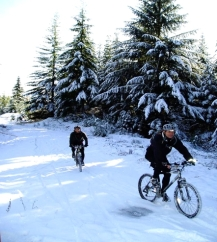 mountain bikers riding a snowy trail