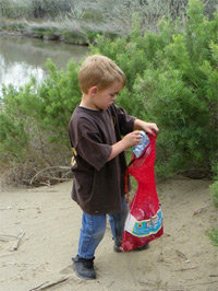 Boy picking up litter at Beverly Dunes