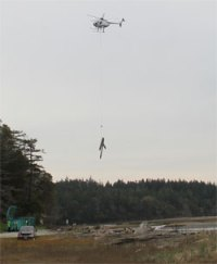 Helicopter hauls load of creosote-treated debris.