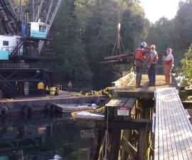 Contractors prepare to pull one of last segments of train trestle across Woodard bay in earlier phase of project in 2010. This location is where large volume of fill currently is being removed to restore natural shoreline. DNR Photo: Lisa Kaufman