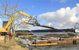 Removing creosote-treated pilings from a barge.