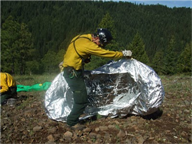 Firefighter demonstrates how to deploy a fire shelter in 25 seconds or less.