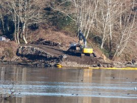 An excavator works to restore native shoreline at Woodard Bay by removing fill. Photo: Michele Zukerberg, DNR.