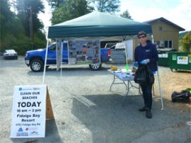 Photo:  Jackson Barnes, WCC Puget SoundCorp member, prepares to greet volunteers for the Aug. 18 cleanup in Fidalgo Bay. Photo: Rose Whitson / DNR