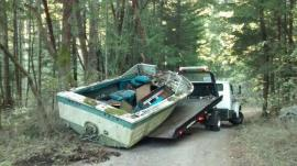 A tow truck pulls an old boat turned into DNR's new program from a forest. Photo by DNR.