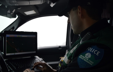 Officer seated with computer in vehicle