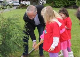 Commissioner Goldmark shows kids how to plant a tree for National Arbor Day.