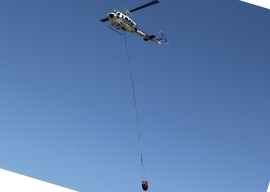 DNR helicopter hovers with a bucket of 250 gallons of water. Photo DNR