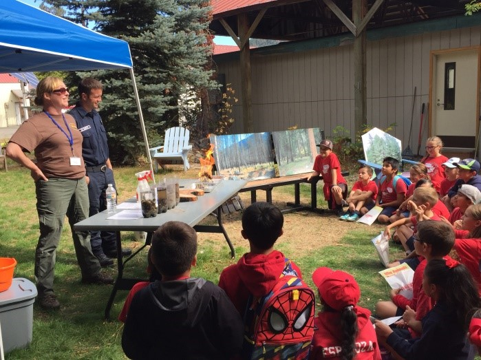 Chumstick Wildfire Stewardship Coalition Director Corrine Hoffman, far left, and Mike Smith, a volunteer coordinator and firefighter with Chelan County Fire District 3, talk to elementary school students about wildfire and its effects on forest ecosystems during the Wenatchee River Salmon Festival last summer in Leavenworth. (U.S. Fish and Wildlife Service photo)